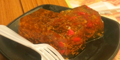 "What our seatmates had for dessert: ""Tonic Medlar and Osmanthus Cake"": A curious concoction; basically, it's like Jell-O with a flower inside."